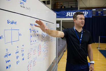 Chris McGown organizes the whiteboard for the coaches attending one of our volleyball clinics.