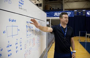 Chris McGown writing practice on the whiteboard during one of our Volleyball Camps