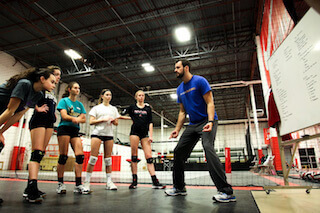 Ryan Newell demonstrates proper defensive posture while coaching at a GMS summer volleyball camp.